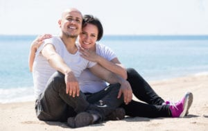mature happy spanish couple smiling holding each other on the beach
